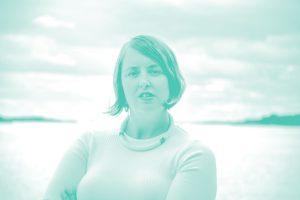 Bild på grundare Josephine Bladh som står med armarna i kors framför havet.
