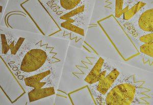 """Bild på tre pappersark som det står """"wow"""" på, skrivet guld och glitter."""
