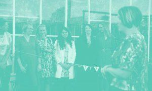 """Metodik/methodology - Bild på grundare Josephine Bladh framför en grupp unga ledare. Ett gäng vimplar med namnet """"makttrampolinen"""" hänger på ett snöre mellan dem."""